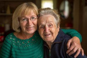 Two elderly women hugging