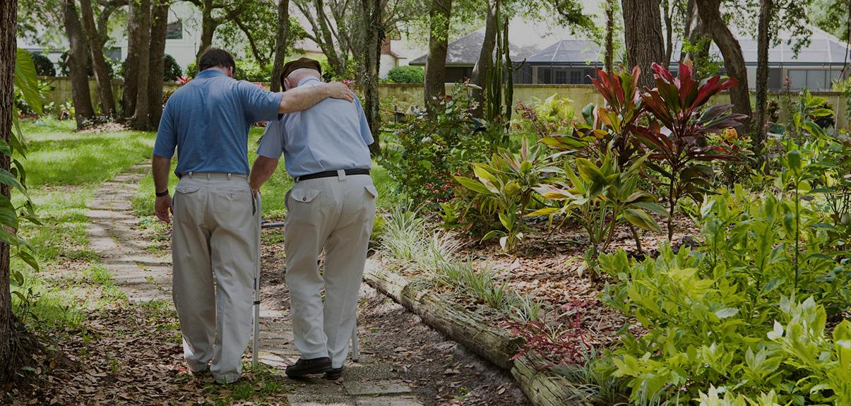 Young man helping elderly man walk