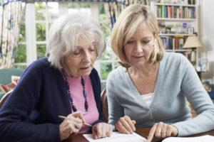 Young woman helping elderly women