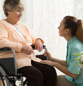 Young woman helping elderly woman in wheelchair