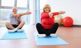 Elderly man and women doing yoga